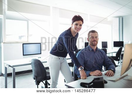 Portrait of teacher and mature student in computer room at college