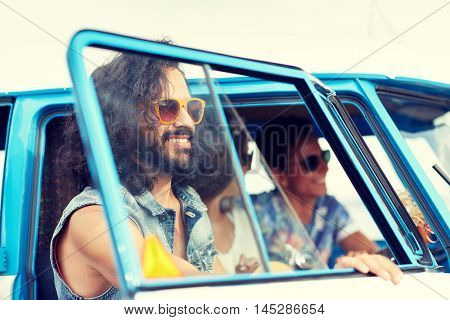 summer holidays, road trip, vacation, travel and people concept - smiling young hippie friends in minivan car