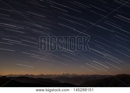 Beautiful night landscape with traces of stars in the form of tracks in the night sky against the background of the contours of mountains and snowy peaks shot with a long exposure