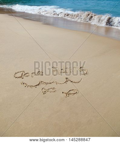 Gone fishing written in the sand at the beach. Holiday concept.