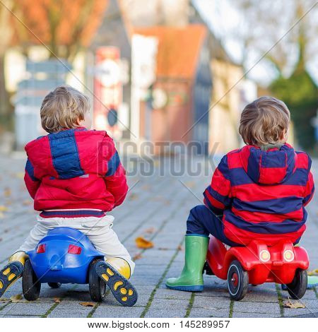 Two little kids in red jackets and rain boots driving colorful toy cars and making competition, outdoors. Kids leisure on cold day in winter, autumn or spring. From back.