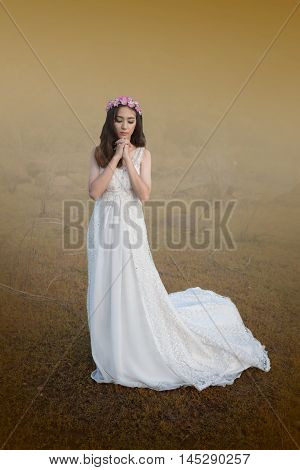 beautiful young woman in white dress with flower on her hair outdoor shot. Portrait of beautiful blond young woman pray for peace