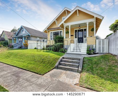 American Craftsman Home With Yellow Exterior Paint.