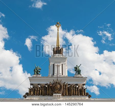 Detail of building with sculptures, coats of arms and flags in the style of the Stalin era