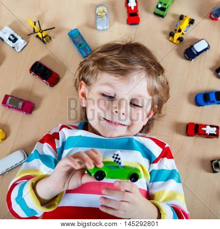 Cute little blond child playing with lots of toy cars indoor. Kid boy wearing colorful shirt. Happy preschool child having fun at home or nursery.