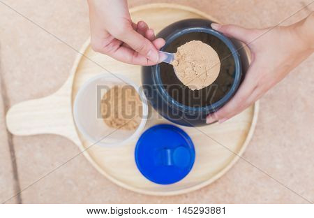 Scoop of whey protein on a wooden plate with jar. on top view