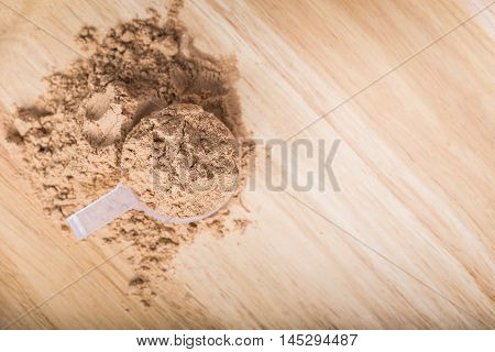 Scoop of whey protein on a wooden plate. on top view