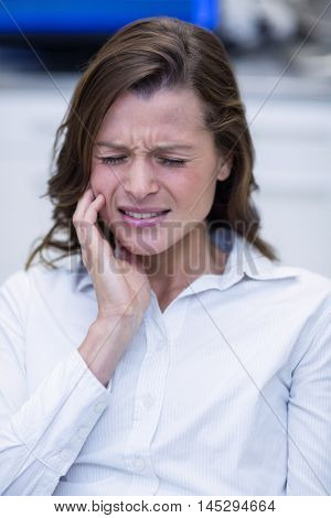 Woman suffering from toothache at dental clinic