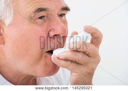 Close-up Of A Man Using Asthma Inhaler