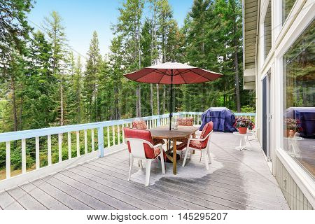 Wooden Walkout Deck After Rain. Furnished With Red Chairs And Table With Umbrella