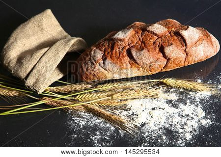 rustic crusty bread and wheat ears on a dark wooden table.