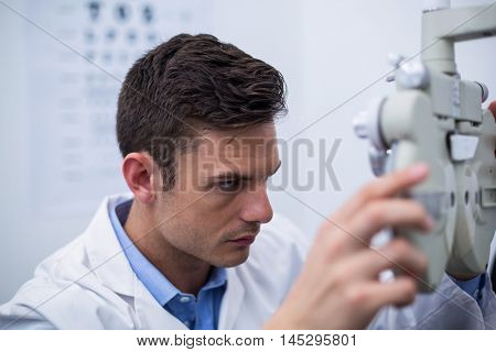 Attentive optometrist looking through phoropter in ophthalmology clinic