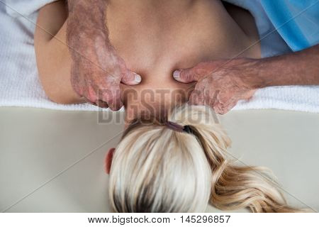 Woman receiving shoulder massage from physiotherapist in clinic