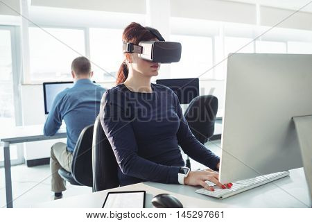 Mature student in virtual reality headset using computer to help with studying at college