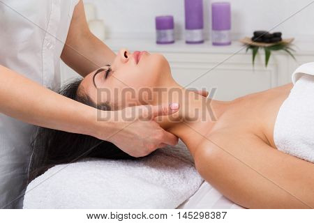 Unrecognizable female beautician doctor with patient in spa wellness center. Professional cosmetologist make body neck massage to beautiful indian girl in cosmetology cabinet or beauty parlor.