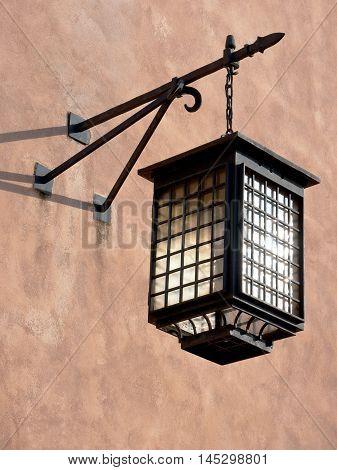 An old municipal lantern hangs on a wall