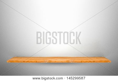 Wooden shelf on grey concrete wall background.
