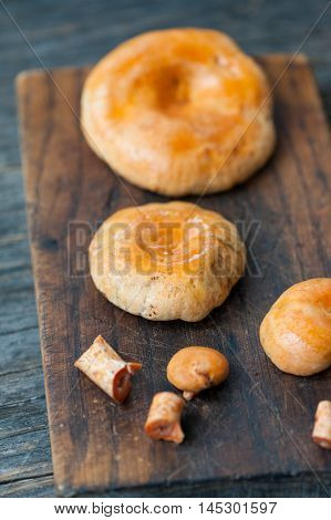 Close up of a bunch of Saffron Milk Cap mushrooms on a wooden table ready to be cooked