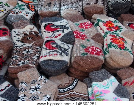 Multi-colored knitted woolen socks are made by national needlewomen for sale at a fair