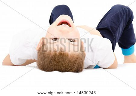 Portrait of a cheerful boy, lying on her back, isolated on white background
