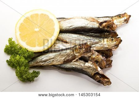 smoked sprats with slice lemon and parsley on bright background