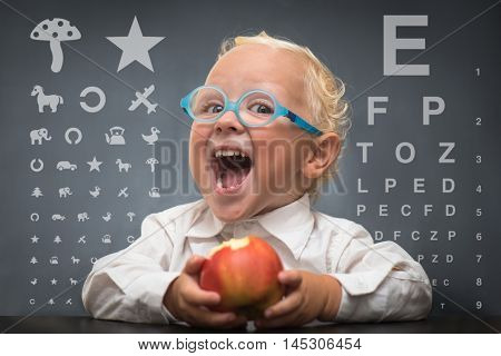 Child with glasses sits at a table on the background of the table for an eye examination