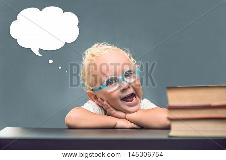 A child wearing in eyeglasses, head over to cloud thoughts