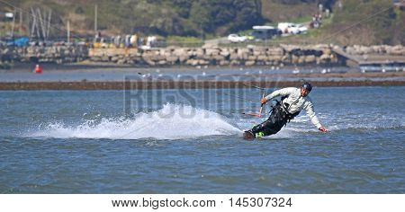 kitesurfer riding his board toeside in Portland Harbour