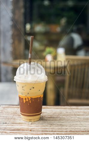Iced Coffee In Takeaway Cup On Wood Table With Blurred Coffee Cafe Background, Selective Focus