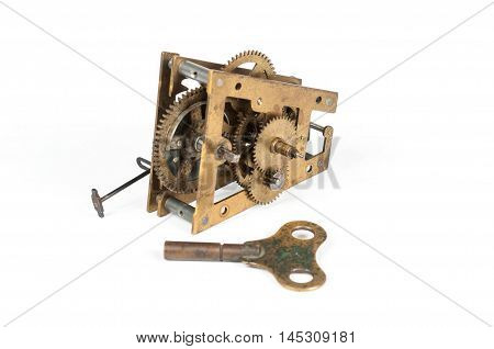 Old brass pendulum clock mechanism with a key.