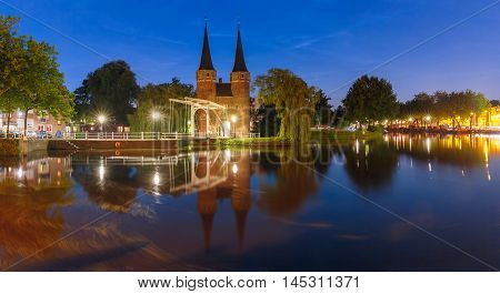 Eastern Gate, Oostpoort, with the white draw bridge, along Delftse Schie canal at night, Delft, Holland, Netherlands