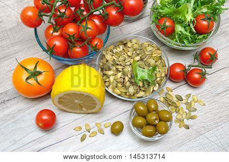 ingredients for preparation of vegetable salad on a wooden background. horizontal photo.