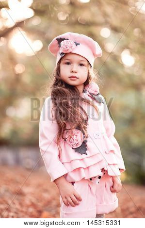 Cute baby girl 4-5 year old wearing stylish winter jacket shorts and hat outdoors. Looking at camera. Childhood. Autumn season.