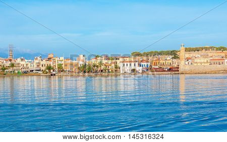 The new port overlooks the old town promenade with its landmarks -Fortezza citadel stone lighthouse at the old harbor colorful cottages Rethymno Crete Greece.