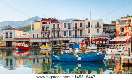 The colorfull fishing boats are moored in the old port adjacent to the tiny cafes and taverns Rethymno Crete Greece.