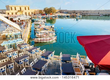 The old harbor is occupied by the tables and chairs of the local outdoor restaurants offering the tasty local cuisine home wine and picturesque views on the wooden fishing boats Rethymno Crete Greece.