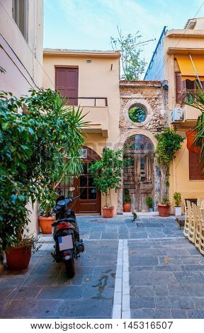 The quiet backstreet of Rethymno with the numerous plants in pots and the view on the old houses' facades Crete Greece.