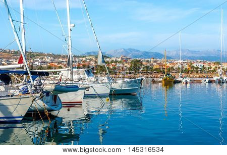 The white yachts reflect in calm waters in the new port Rethymno Crete Greece.