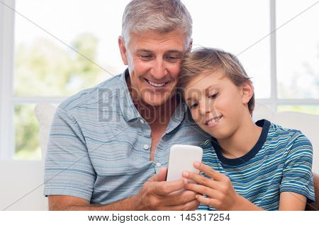 Grandfather and grandson using mobile phone at home. Boy helping senior man surfing net with smart phone. Grandfather and grandchild checking their photos on new phone.
