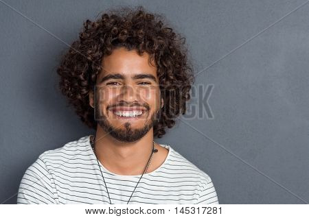 Portrait of a happy cheerful young man looking at camera. Handsome man with beard and curly hair standing against grey background. Close up face of multi ethnic young man isolated against grey wall.
