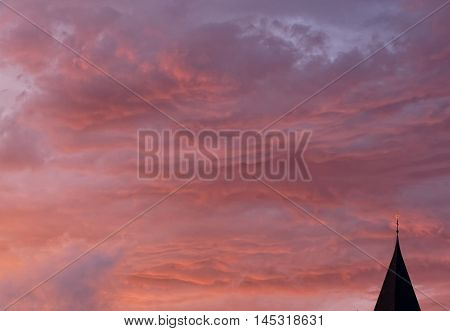 Dramatic cloads over a church tower glowing red in the evening sun