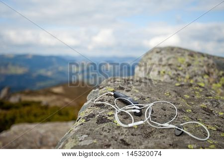 white earphones with mp3 on moss-covered stone Carpatian