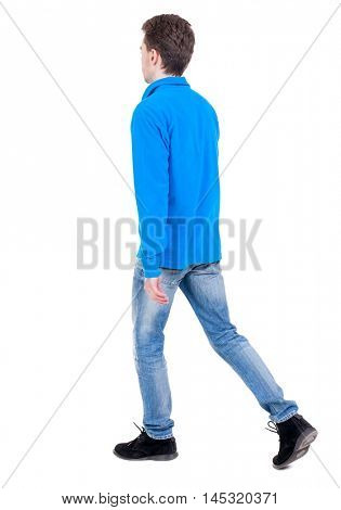 Back view of going handsome man. walking young guy . Curly boy in blue sweater goes out of the frame.