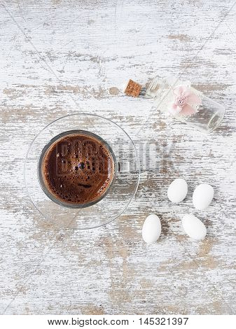 Turkish coffee and almond candy on a white wooden background