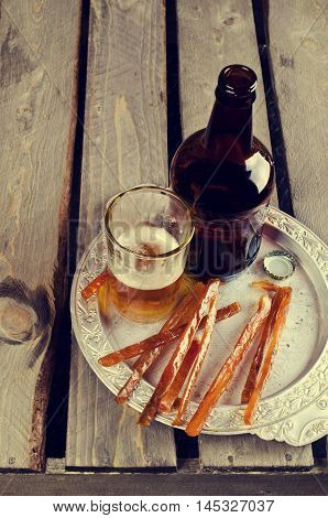 Thin sticks of smoked fish on the wooden background. Selective focus.