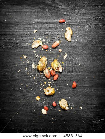 Shelled peanuts with the shell. On the black wooden table.