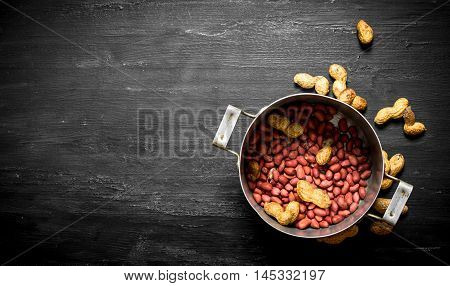 Peanuts in the old pot. On the black wooden table.