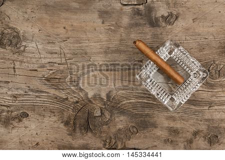 Glass ashtray with cigar stands on a wooden surface can be used as background