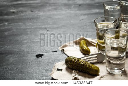 Glasses with vodka and pickled cucumbers on the old fabric. On a black wooden background.