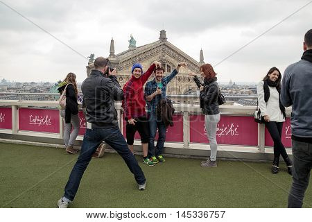 PARIS, FRANCE - MAY 15, 2015: Group of unknown young people are posing in front of a photographer on the roof of the Galeries Lafayette.